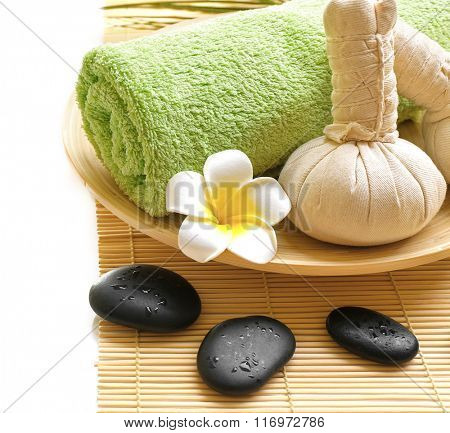 Beautiful spa composition. Herbal balls and towel in the bowl. Pebbles and cosmetics close up