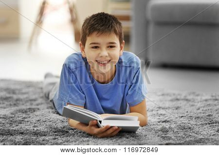 Boy with book lying on a floor at home