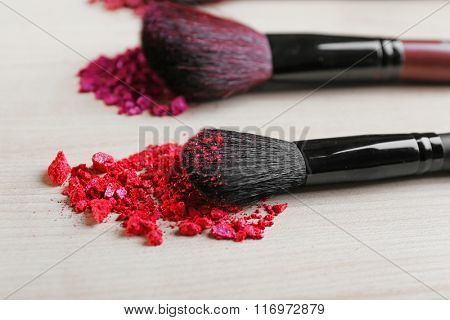 Makeup tools with powder on a wooden background, close up