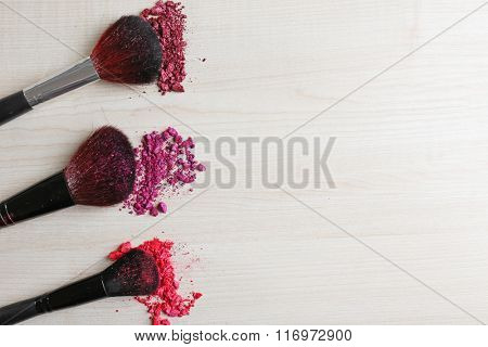 Makeup tools with powder on a wooden background