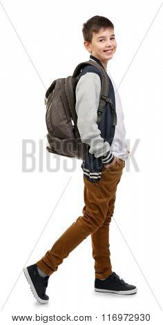 Cute little boy with grey backpack going right, isolated on white