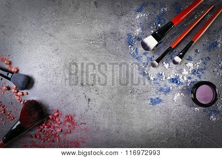 Makeup brushes with shadows and pink rouges on gray background closeup
