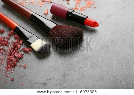 Makeup brushes with red lipstick and rouge on gray background closeup