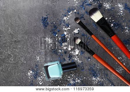 Makeup brushes with blue nail polish and shadows on gray background closeup