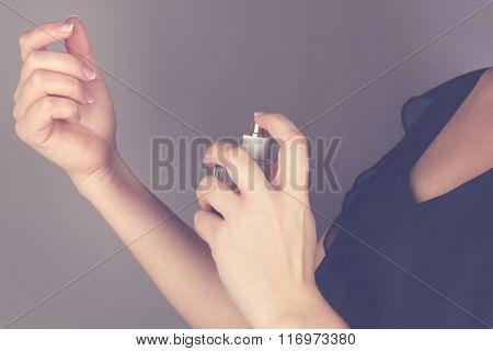 Young woman applying perfume on her wrist