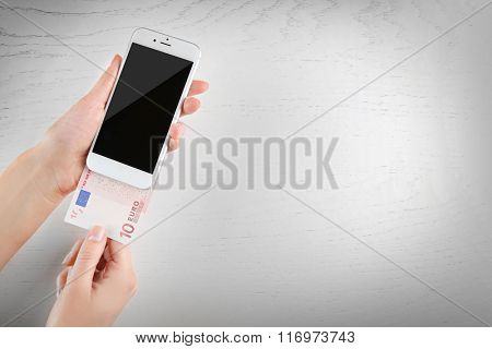 Hands holding smart phone and euro banknote on light table. Telephone charges