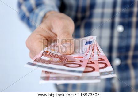 Man holding euros in hand