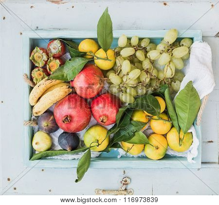 Various colorful tropical fruit selection in blue wooden tray, top view, horizontal