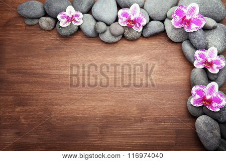 Spa stones and orchids on wooden background