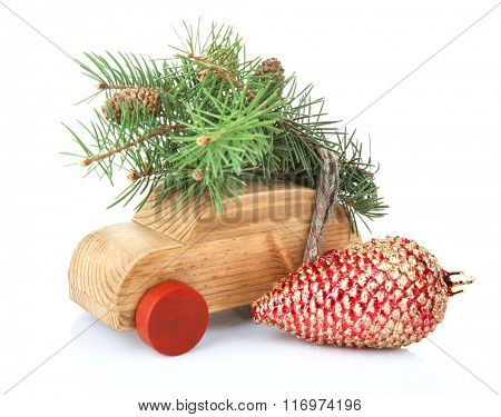 Wooden toy car with fir sprigs and cone, isolated on white