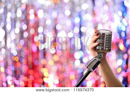 Female hands holding microphone against bright glitter background