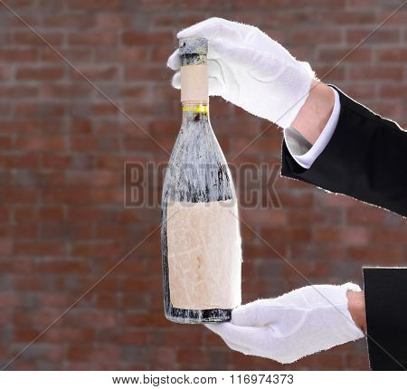 Man holding an old bottle of champagne in hands on brick wall background