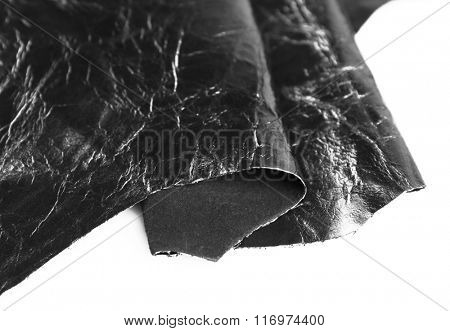 Black shiny leather texture on white background, close up