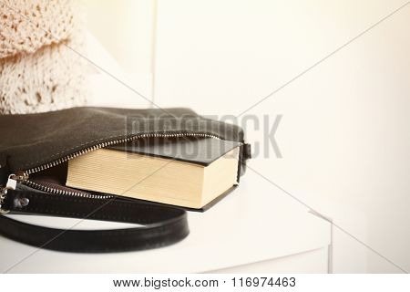 Fashion female handbag with book on white chair, close up