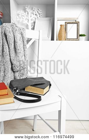 Fashion female handbag with books on white chair