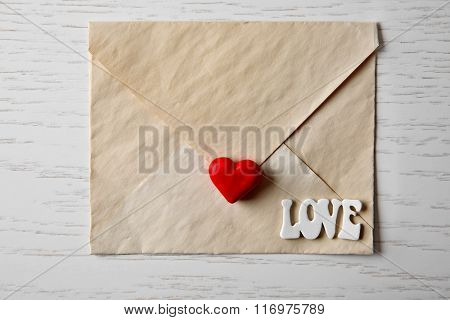 Blank envelope with heart on wooden background