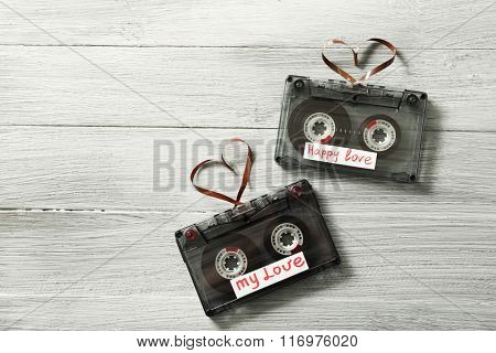 Retro audio cassettes with tapes in shape of hearts on wooden background
