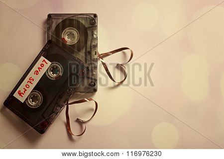 Retro audio cassettes with tapes in shape of hearts on white background