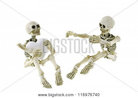 Soft focus of Skeletons sitting together with one holding a white heart, Focusing on a heart, isolated on white
