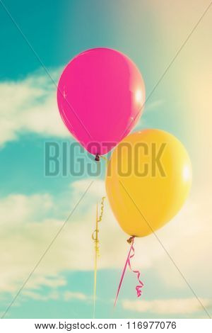pink and yellow balloons against sky with clouds, closeup