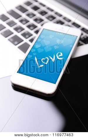 Tablet and mobile phone with romantic screensaver on keyboard