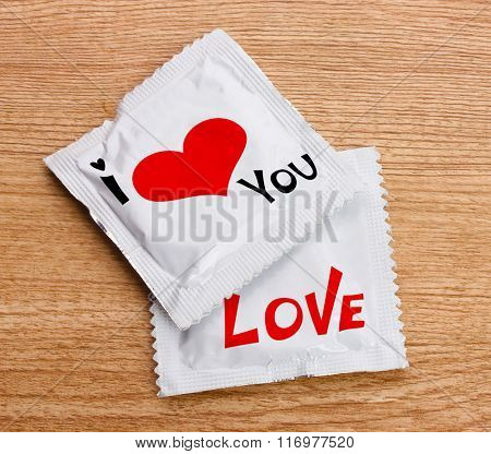 Condoms with text I love you on wooden table