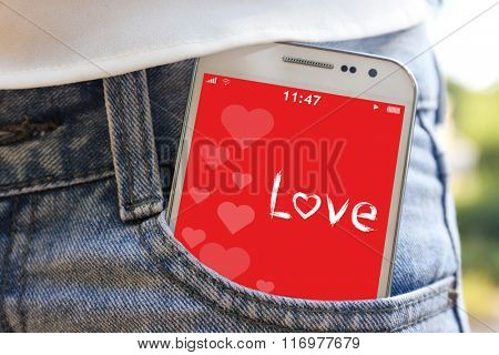 White smart mobile phone with romantic screensaver  in jeans pocket
