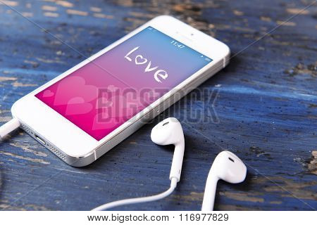 Mobile phone with romantic screensaver and earphones on wooden background