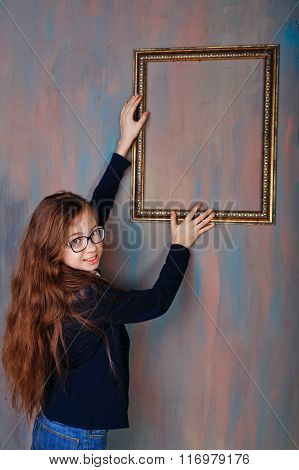 Girl Teenager Corrects An Empty Picture Frame.