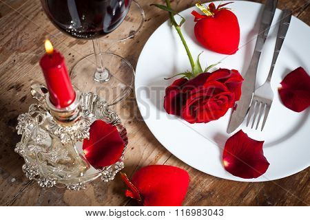 Table setting with red rose on plate