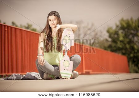 Teenage Girl Skater Riding Skateboard On Street.