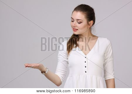 Woman showing a product. Empty copy space on the open hand palm.