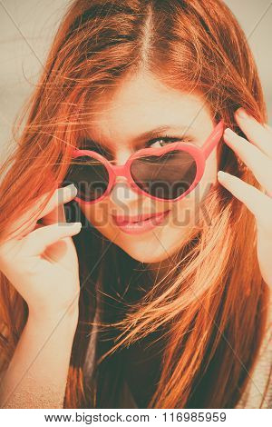 Beautiful redhaired happy girl in heart shaped sunglasses on beach.