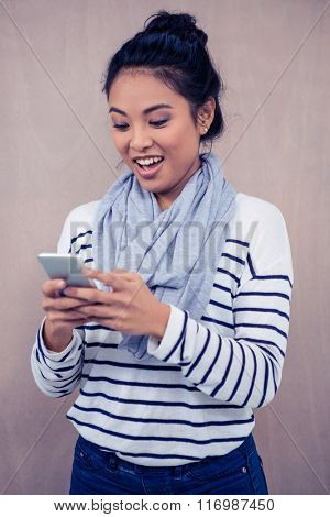 Surprised Asian woman using smartphone standing