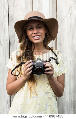 Young smiling woman posing with a camera