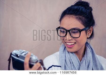 Smiling Asian woman wearing eyeglasses taking selfie with camera
