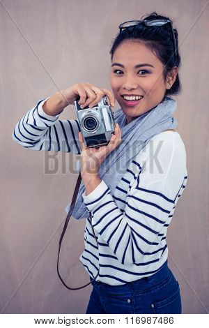 Smiling Asian woman taking photograph with camera and looking at the camera