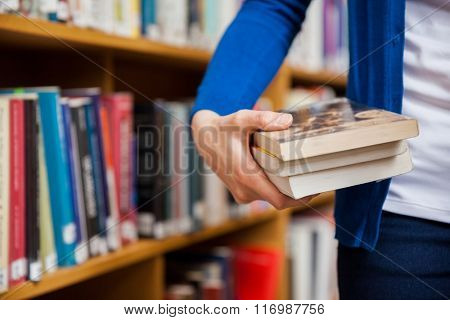Happy female student taking books in the library at the university