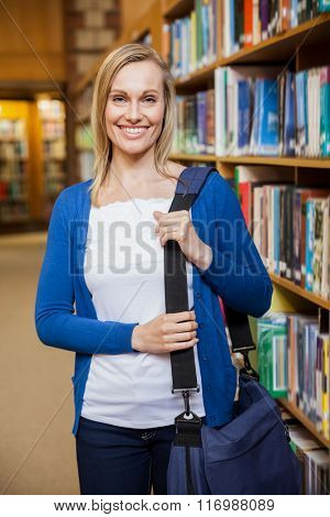 Smiling female student posing in the library at the university