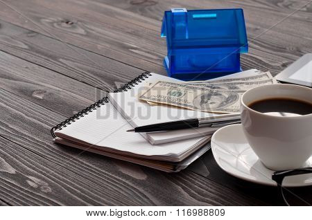 Notebook With A Pen, Cup Of Coffee, Money And House