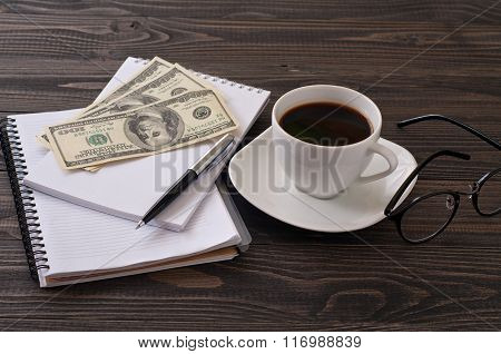 On Wooden Office Desk, Stack Notepads, Pen, Coffee And Money