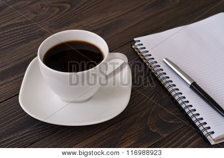 American Cup Of Coffee With Notebook And Pen