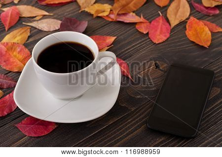 American Cup Of Coffee With Fallen Autumn Leaves And Smartphone