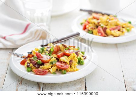 Scrambled eggs with peas, bacon and tomatoes