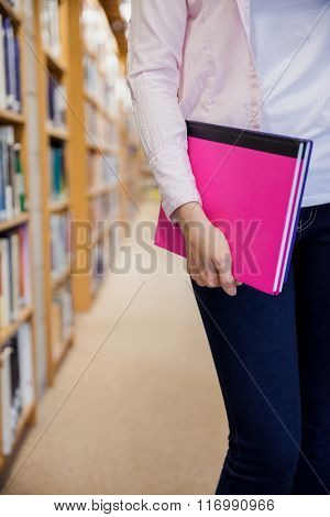 Female student holding textbooks in the library at the university