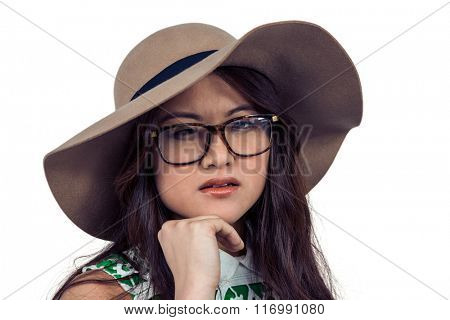 Asian woman with hand on chin wearing hat on white screen