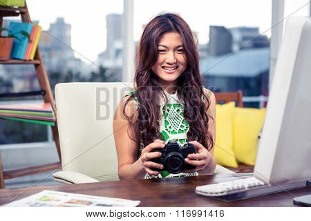 Smiling Asian woman holding camera in office