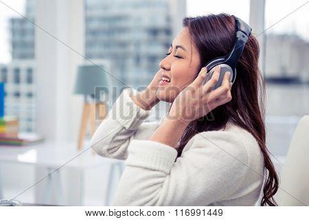 Asian woman using headphones in office