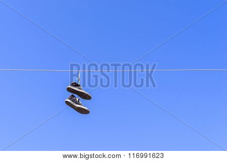 Old Gym Shoes On A Wire Against The Blue Sky
