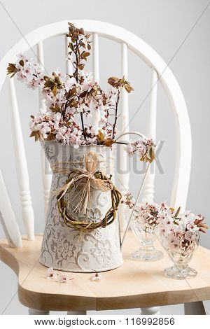 Springtime cherry blossom in decorative jug sitting on chair